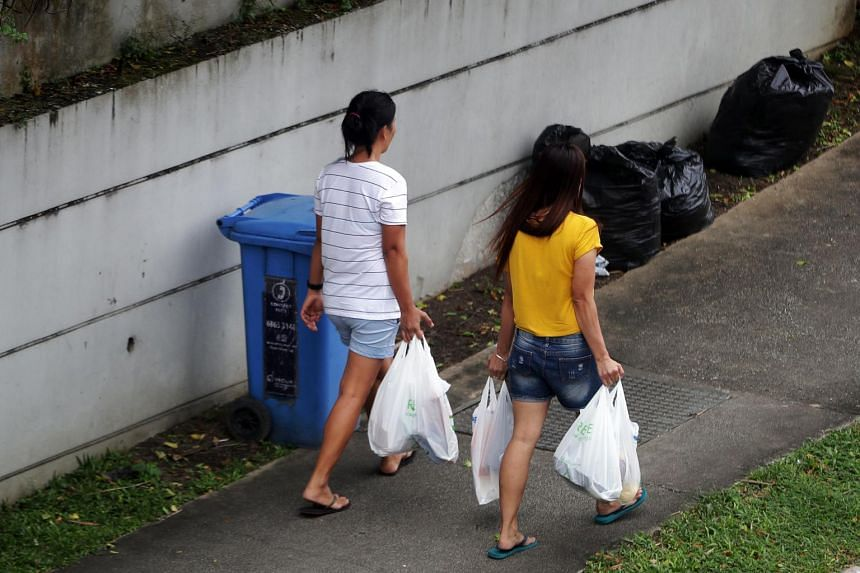 Women carrying plastic shopping bags near Holland Village.