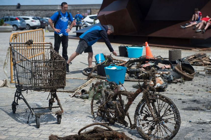 Volunteers stand next to waste collected from the sea.