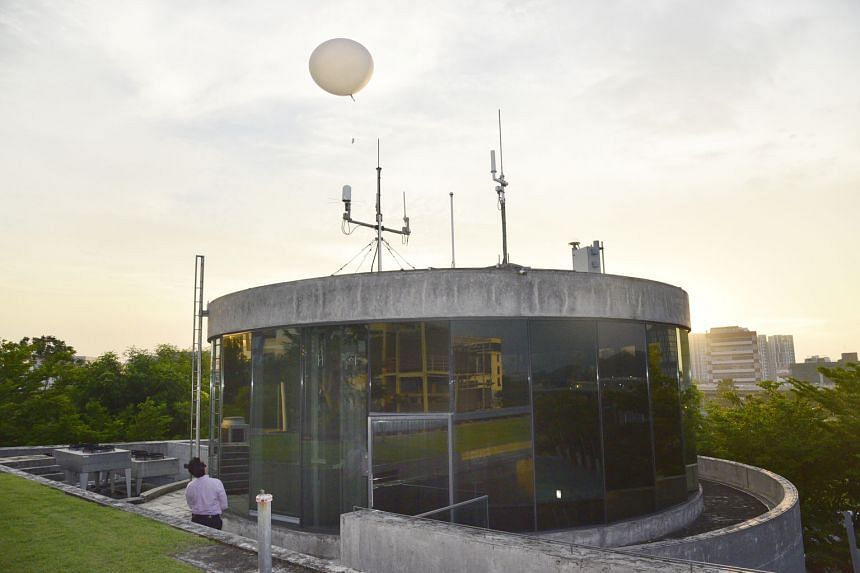 A staff member mounting the radiosonde to the weather balloon at the Centre for Climate Research Singapore. The weather balloon is released twice a day at the Centre for Climate Research Singapore, except during thunderstorms. Erratic weather results