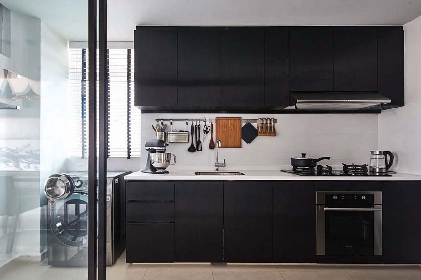 At first glance, the black laminate cladding the kitchen cabinetry appears to be matte. However, it has a striped, stainless steel-like finish, with its sheen offering visual interest in an otherwise simple kitchen.