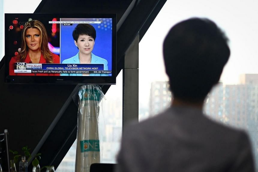 China's state broadcaster CGTN anchor Liu Xin looks at a screen showing her debate with Fox Business Network presenter Trish Regan, at the CCTV headquarters in Beijing on May 30, 2019.