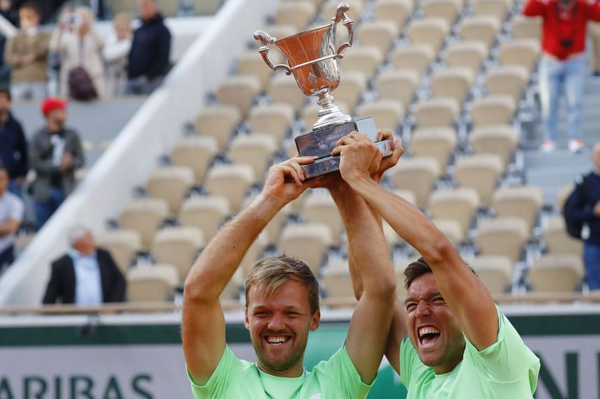 Germany's Kevin Krawietz and Andreas Mies celebrate with the trophy.