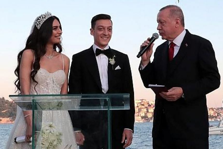 German footballer Mesut Ozil and wife Amine Gulse, 26-year-old actress and former Miss Turkey, listening to a speech by his best man and Turkish President Recep Tayyip Erdogan, during the wedding ceremony in Istanbul on Friday. The 30-year-old Ozil,