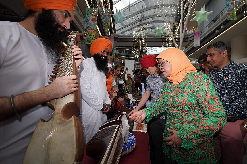 President Halimah Yacob at a booth featuring traditional music instruments during the launch of Sikh Heritage Day at Our Tampines Hub yesterday.
