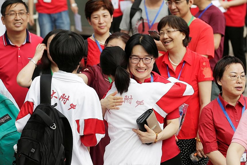Teachers hugging students as they arrived for the first part of China's annual national college entrance exam in Beijing on Friday. Despite concerns among parents and students over strained US-China ties, experts say they do not expect the number of