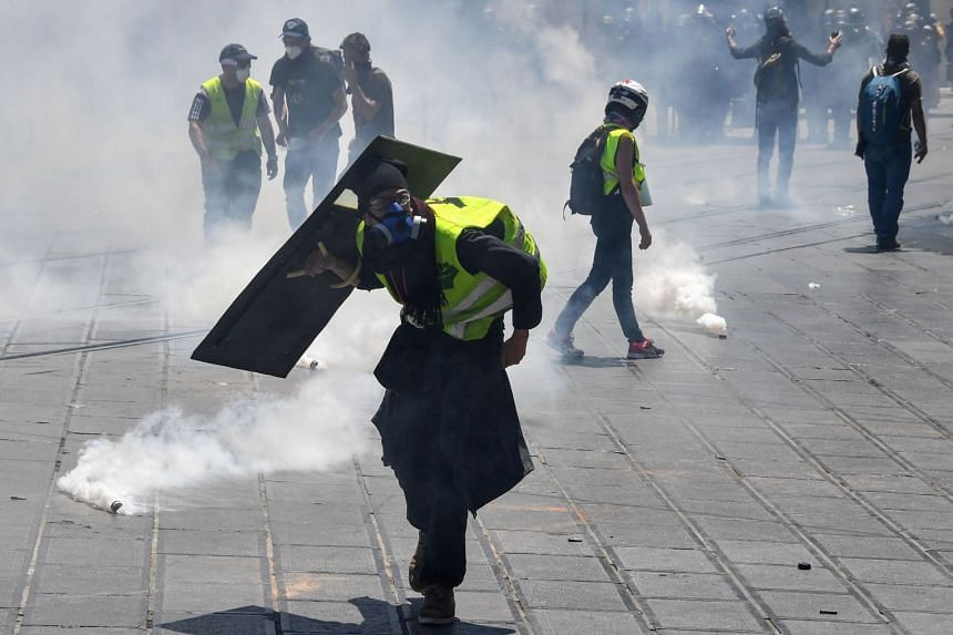 People protect themselves from to tear gas canisters thrown by police in Montpellier, southern France.
