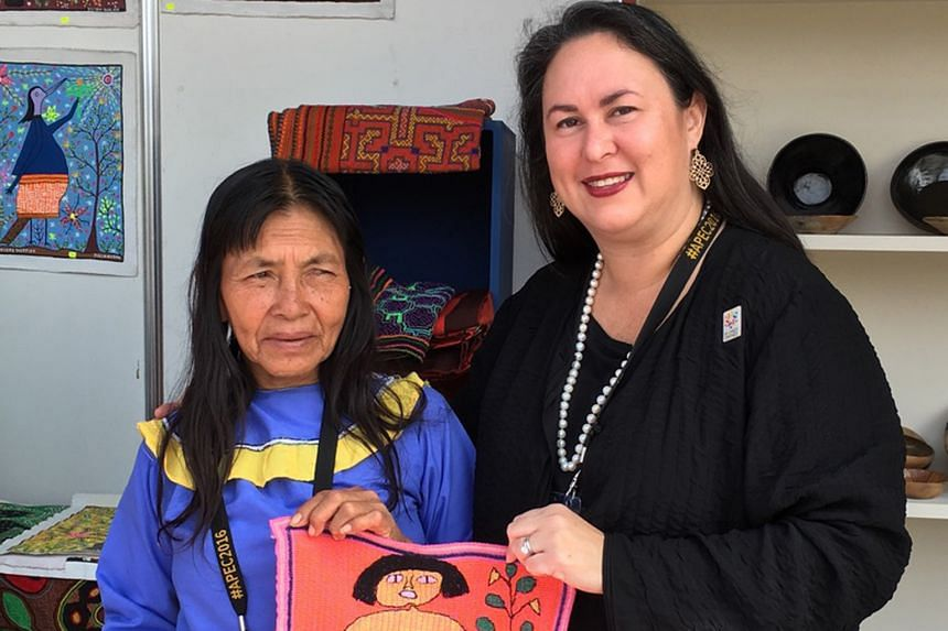Ms Vazquez with a woman business owner from Peru in 2016. One lesson she has learnt is never to assume the potential of what women in any business big or small are capable of doing. PHOTO: COURTESY OF ELIZABETH VAZQUEZ