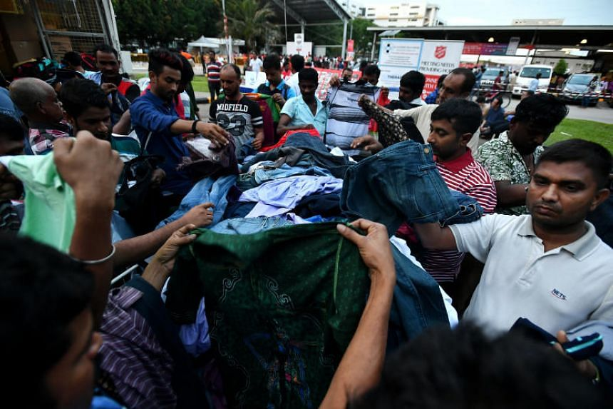 Migrant workers choosing clothes to buy from the Salvation Army at the MWC Recreation Club @ Soon Lee, on June 9, 2019.