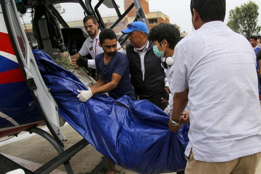 Nepali officials unload bodies of Everest climbers at the helipad of the Teaching Hospital in Kathmandu, Nepal, on May 23, 2019.
