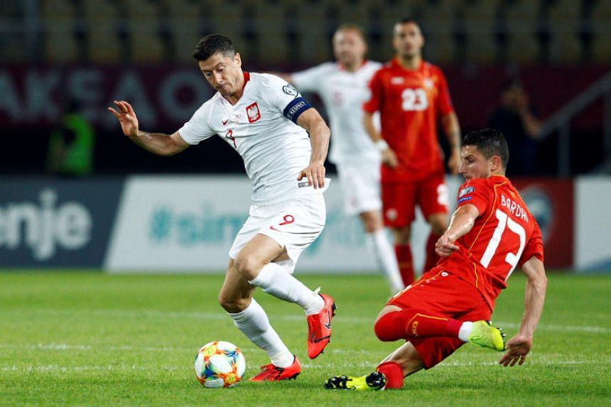 Poland's Robert Lewandowski (left) dribbling the ball as North Macedonia's Enis Bardhi tries to tackle him, during their Euro 2020 qualifier in Skopje, North Macedonia, on June 7, 2019.