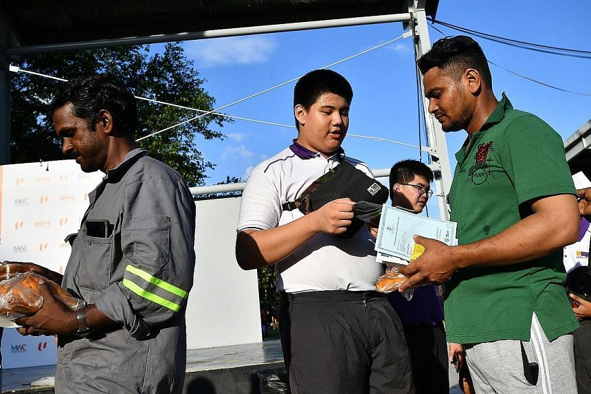 Spectra Secondary School student Keith Tay presenting a thank-you card to Mr Rubel Sheikh, 32, a rigger from Bangladesh, at yesterday's event. Migrant workers collecting goodie bags at this year's NTUC May Day Migrant Workers Celebration, held at its