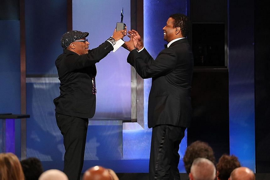 Director Spike Lee (left) presenting Denzel Washington with the American Film Institute's Life Achievement Award last week in Los Angeles, where the actor was honoured for opening the door for black movie stars.