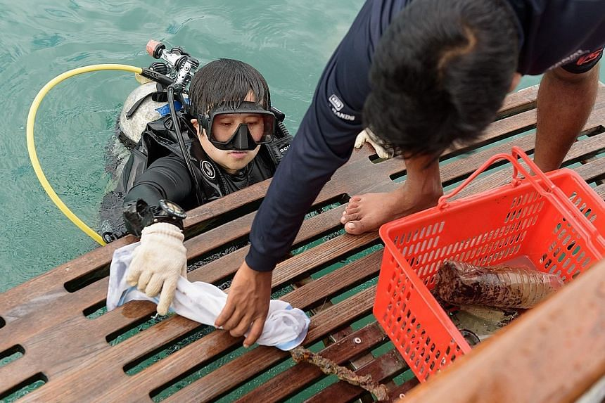 A volunteer diver with the marine debris collected underwater. Yesterday, 20 volunteer divers completed a clean-up exercise in the southern waters around Lazarus Island. PHOTO: MARITIME AND PORT AUTHORITY