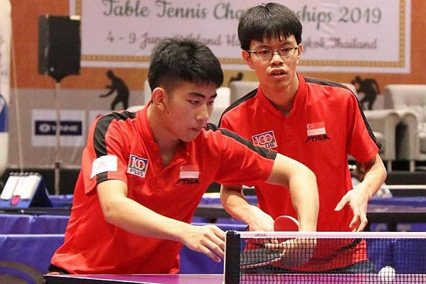 Left-hander Koen Pang (left) gets ready for a backhand return as Josh Chua watches in the junior boys' doubles final in Bangkok. Pang's coach Gao Ning is pleased with his progress.