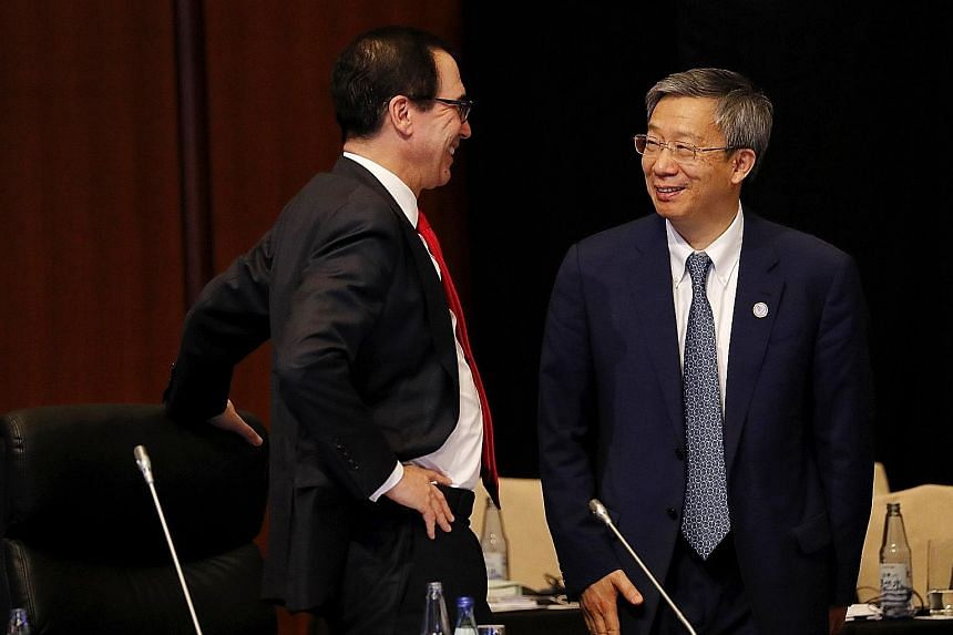 People's Bank of China governor Yi Gang with US Treasury Secretary Steven Mnuchin at a meeting of Group of 20 finance ministers and central bankers in Fukuoka on Saturday. Mr Mnuchin tweeted that they had a candid and constructive discussion.