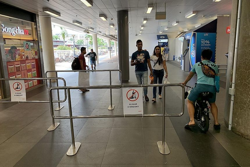 A man riding his personal mobility device through a gap in the metal barriers, which were set up to get riders to dismount inside the Woodlands MRT station compound. SMRT is trialling the use of such barriers to improve safety for commuters. ST PHOTO