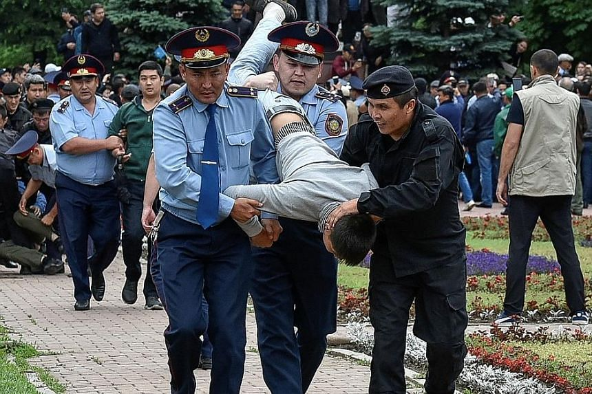 Police officers restraining and detaining protesters during a rally in Kazakhstan's largest city Almaty yesterday. Hundreds of people protested against the presidential election in Almaty and the capital Nur-Sultan, criticising it as undemocratic.