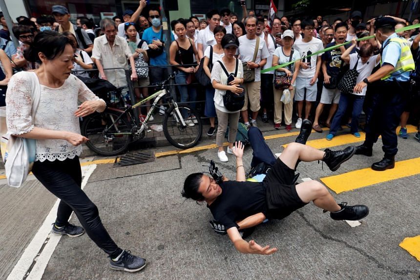 A police officer detains a demonstrator during a protest during a march against a controversial extradition law proposal in Hong Kong on June 9, 2019.