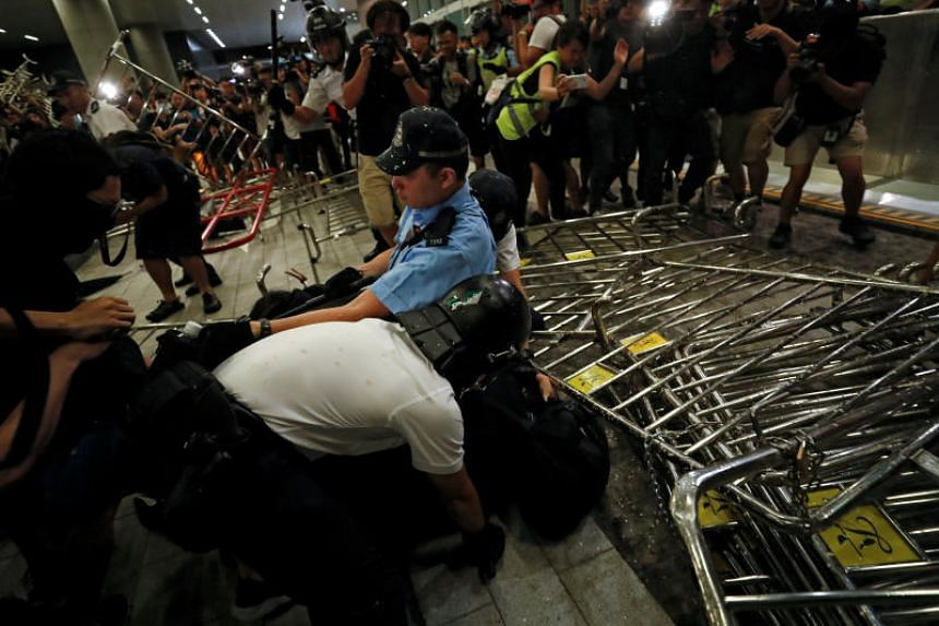Riot police detains a demonstrator during a protest to demand the authorities scrap a proposed extradition Bill with China, in Hong Kong, on June 10, 2019.