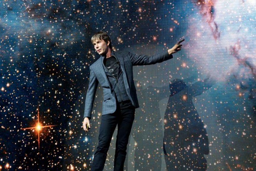 Professor Brian Cox uses pictures from telescopes and space probes to illustrate his lecture.