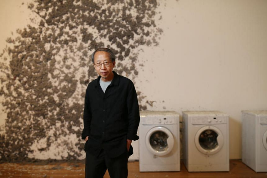 Performance and installation artist Huang Yong Ping with his work titled Reptiles, which consists of washing machines and giant, greyish forms sculpted from newspaper pulp.