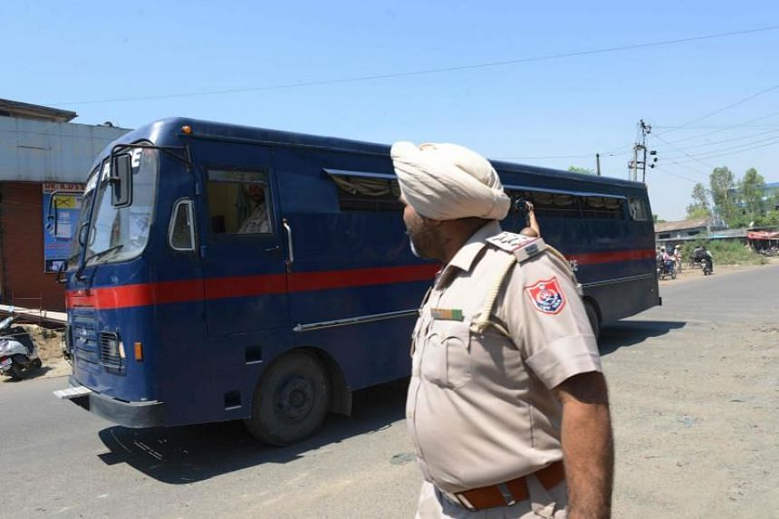 Indian Punjab Police personnel escort a police vehicle carrying the seven accused on June 10, 2019. Six of them were convicted while one was found not guilty.