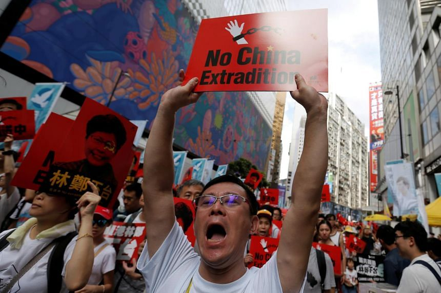 A demonstrator holds up a sign during a protest to demand authorities scrap a proposed extradition bill with China, in Hong Kong, on June 9, 2019.