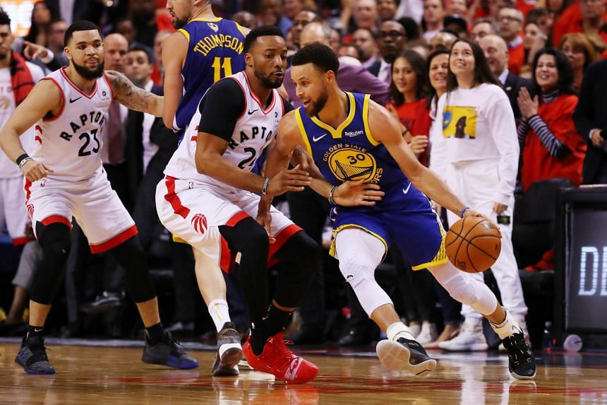Stephen Curry of the Golden State Warriors (in blue) in action against the Toronto Raptors at the Scotiabank Arena, on June 10, 2019.