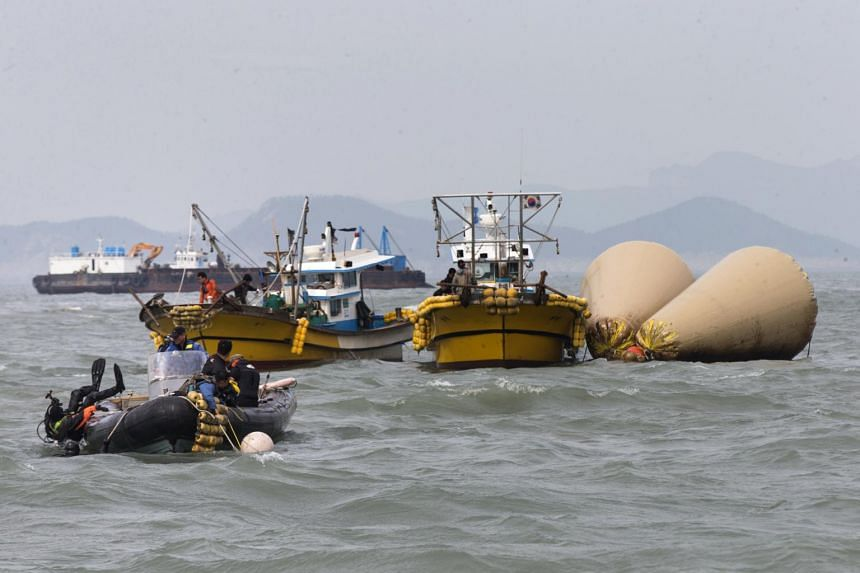 Divers enter the water next to buoys marking the site of the submerged Sewol ferry near Jindo, South Korea, on April 21, 2014.