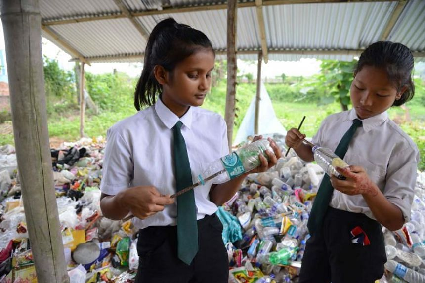 Students put plastic bags inside plastic bottles to make eco-bricks which will be used for construction purposes at the Akshar Forum school in Pamohi on the outskirts of Guwahati on May 20, 2019.