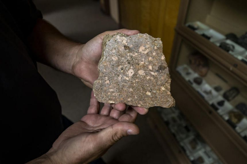An employee displays a piece of raw ore pulled from the Mountain Pass mine, in Mountain Pass, California, US, on Friday, June 7, 2019.
