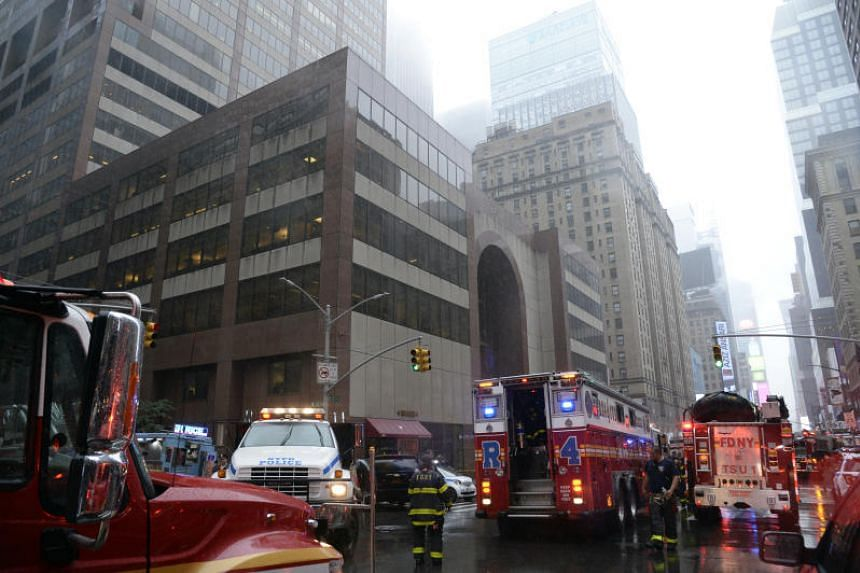 Firefighters at the scene after a helicopter crashed atop a building and caused a fire in the Manhattan borough of New York on June 10, 2019.