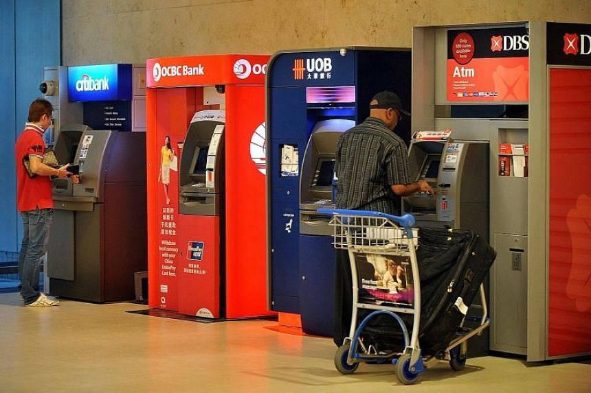 Patrons using ATM machines at Changi Airport.