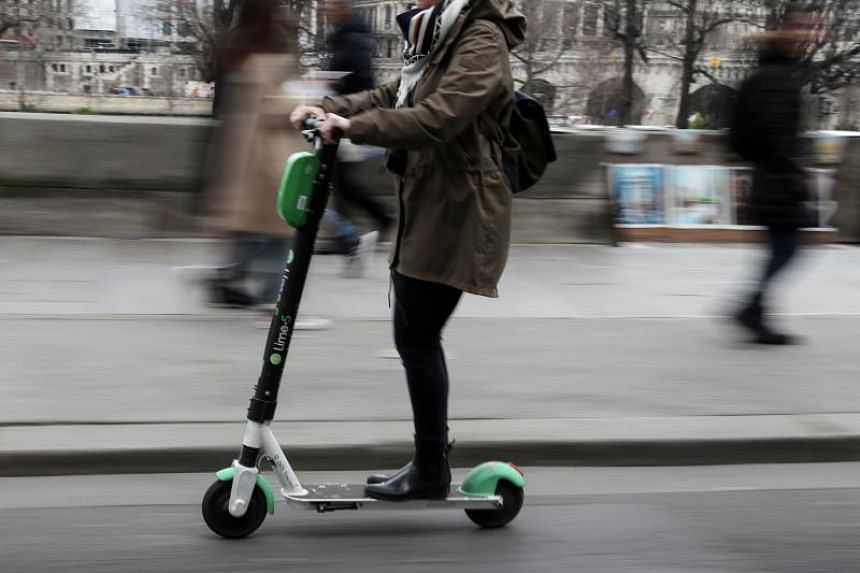 A woman uses an Lime-S electric scooter of the US company Lime in Paris on March 3, 2019.