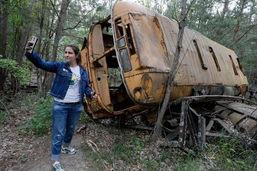 A visitor takes a selfie with an abandoned bus during a Chernobyl tour