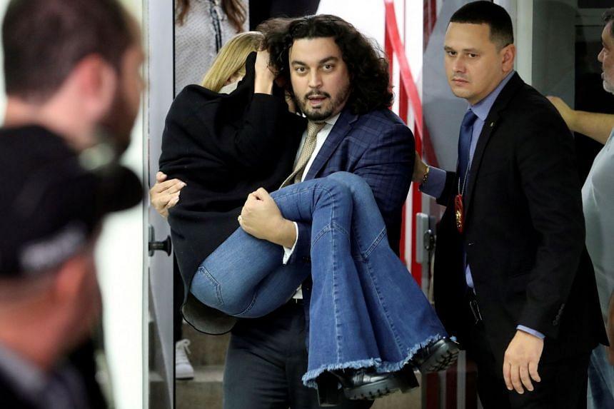 Lawyer Danilo Garcia de Andrade carries Najila Trindade de Souza after she gave testimony at a police station in Sao Paulo.