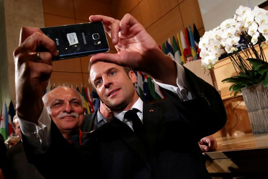 Macron takes a selfie during the annual labour conference in Geneva, Switzerland.