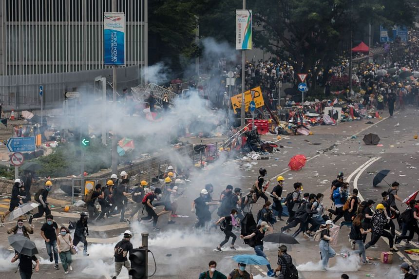 Protesters run as tear gas canisters are fired during the rally.