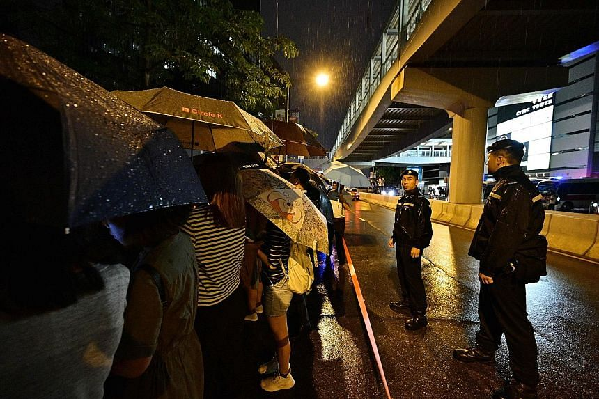 Above: Police standing guard as protesters sang hymns outside the government headquarters yesterday. Left: A group of assistants to members of the Legislative Council speaking to the media outside the LegCo building. Police officers checking the pers