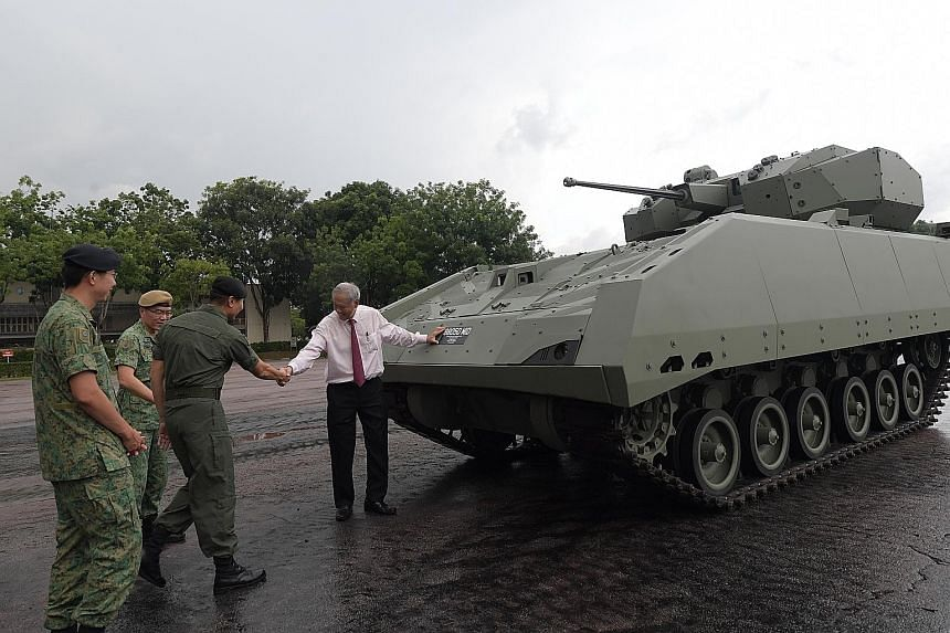 Former servicemen from the armour formation posing for photographs with the Hunter, the army's latest armoured fighting vehicle, at Sungei Gedong Camp yesterday. The vehicle is locally designed and developed by the DSTA with ST Engineering and the ar