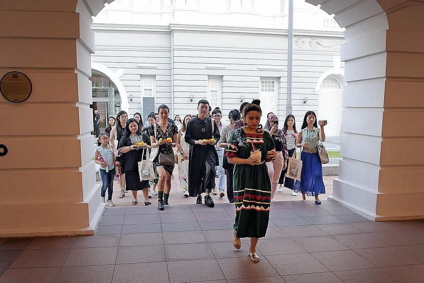 Home-grown artist Zarina Muhammad (foreground) leading members of the press in a ceremonial welcome ritual at the preview of StoryFest on Monday.