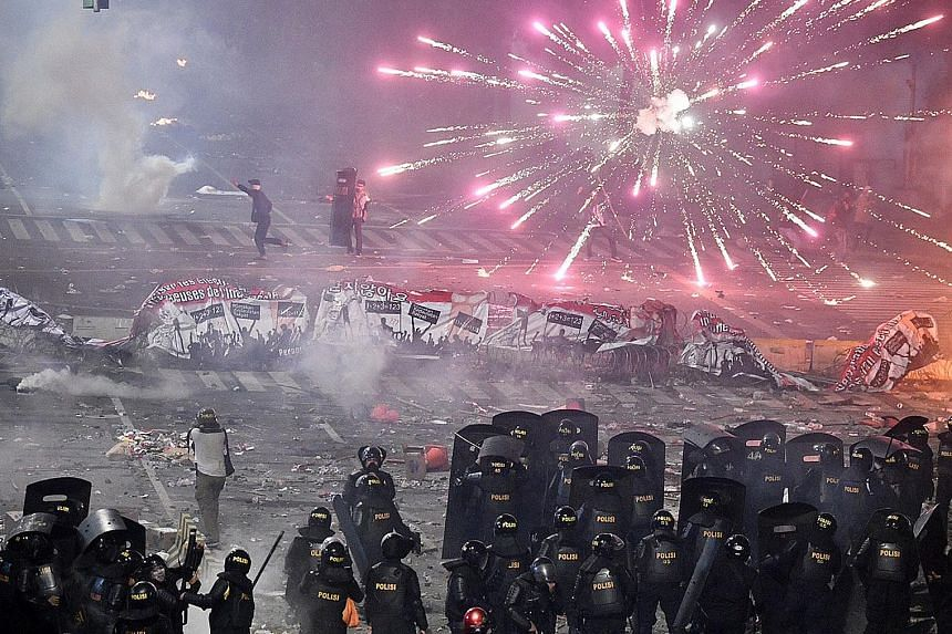 Retired general Kivlan Zen, who is in police custody, was allegedly behind the plot to kill four senior state officials and a high-profile pollster. Protesters shooting fireworks at police during clashes in Jakarta last month. According to statements