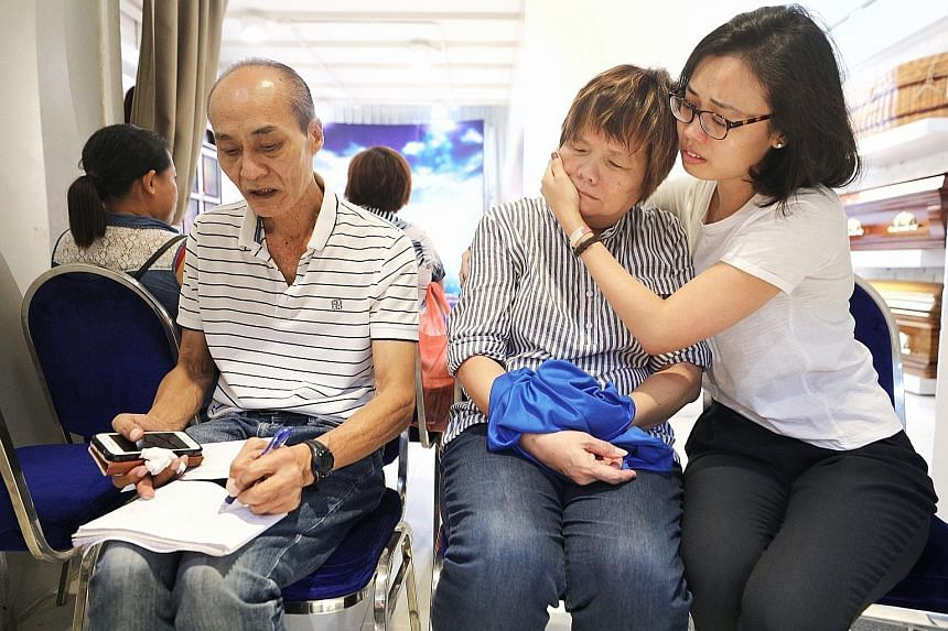 Mr Tung, who worked at rooftop bar 1-Altitude, fell into a 4m-deep pit on the roof of One Raffles Place and died. Security guard Shaun Tung's father Tung Kim Swee, mother Chan Lian Poh and sister Rebecca at his wake in Geylang Bahru.