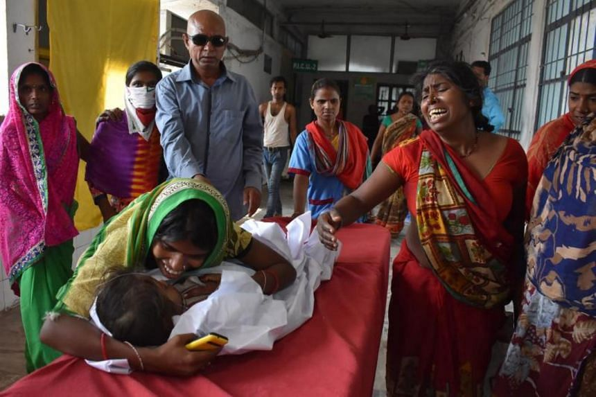 A child arrives in a hospital due to Acute Encephalitis Syndrome as family members react in Muzaffarpur, India, on June 10, 2019.