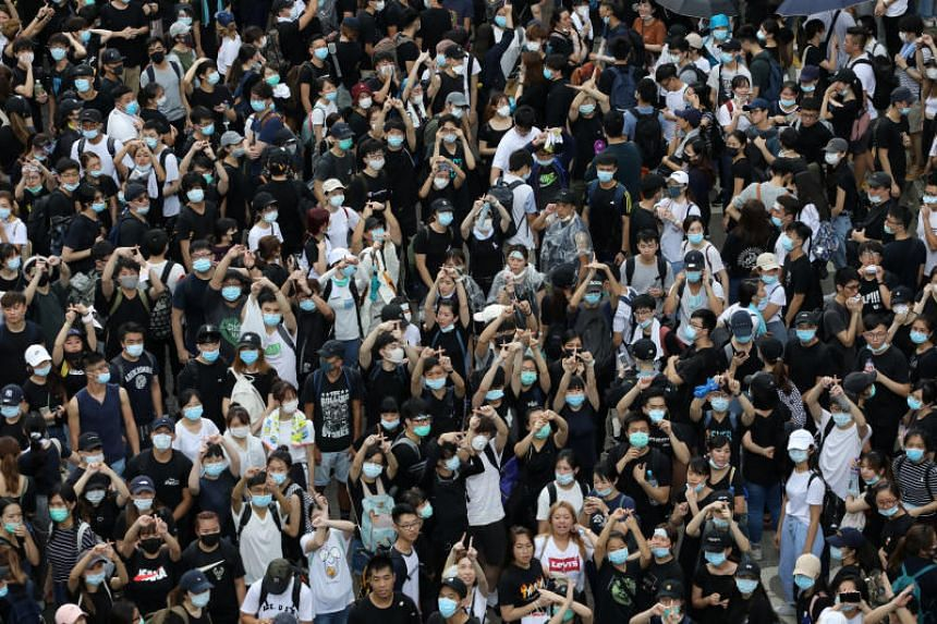 Protesters gesture during a march along a road demonstrating against a proposed extradition Bill in Hong Kong on June 12, 2019.