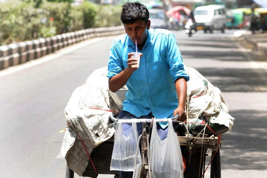 An Indian man hydrates himself while pulling a fruit cart during a hot afternoon in New Delhi, India, on June 11, 2019.