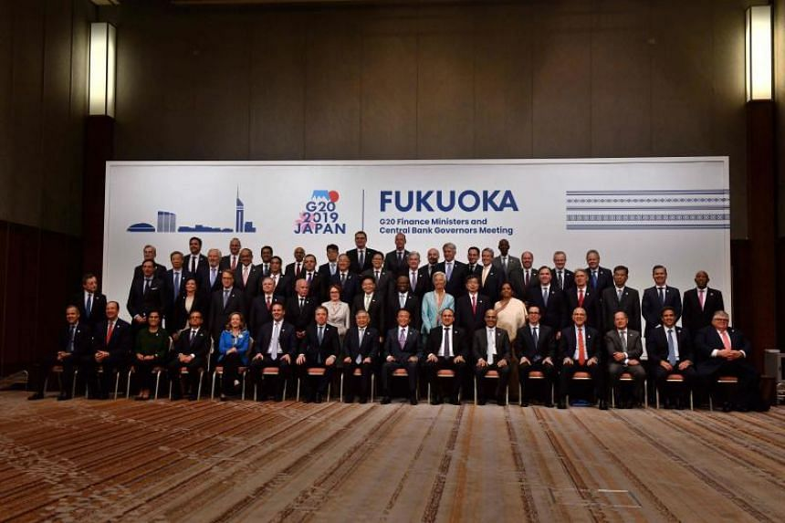 Japan's Finance Minister Taro Aso poses with delegations members for a family photo during the G20 Finance Ministers and Central Bank Governors Meeting in Fukuoka, Japan on June 9, 2019.