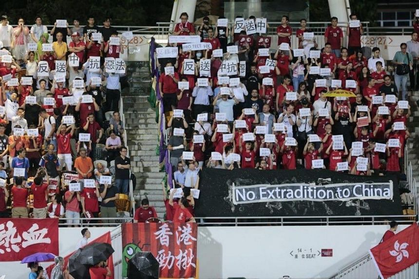 Hong Kong football fans held signs opposing government plans to allow extraditions to the mainland at a home match against Taiwan on June 11, 2019.