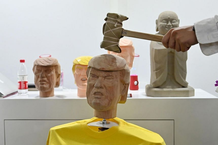 A man hits a bobble head in the likeness of US President Donald Trump as part of a stress relief station from a Japanese company during the Consumer Electronics Show in Shanghai on June 11, 2019.