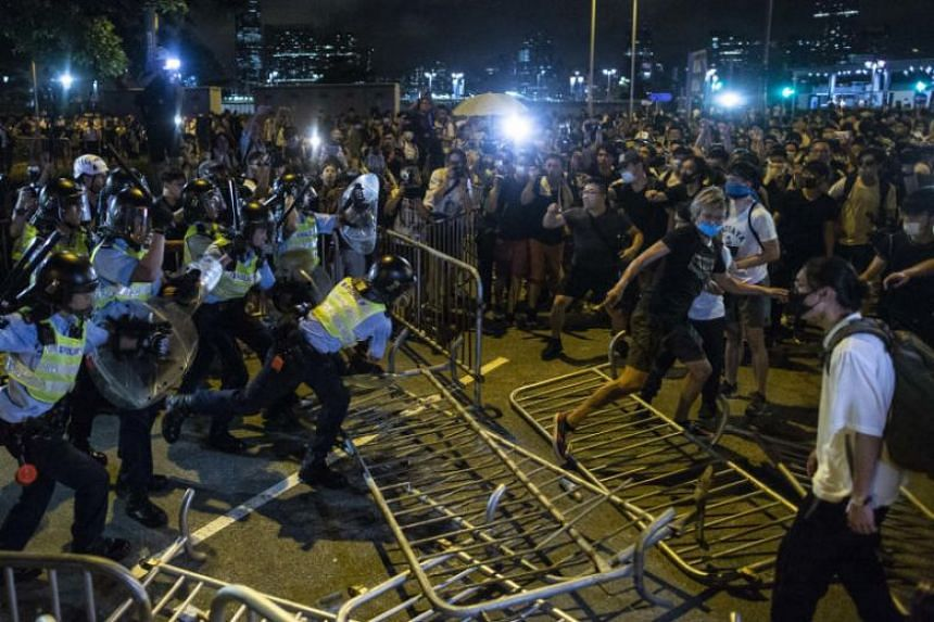 Riot police officers clash with demonstrators during a protest against the government-proposed extradition Bill, outside the legislative council building, on June 9, 2019.